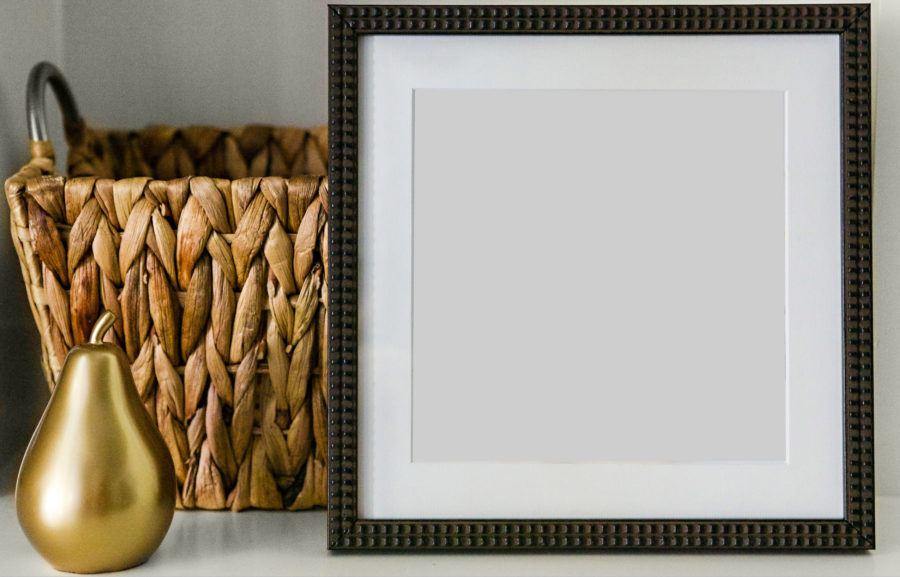 Square photo frame by a basket and pear